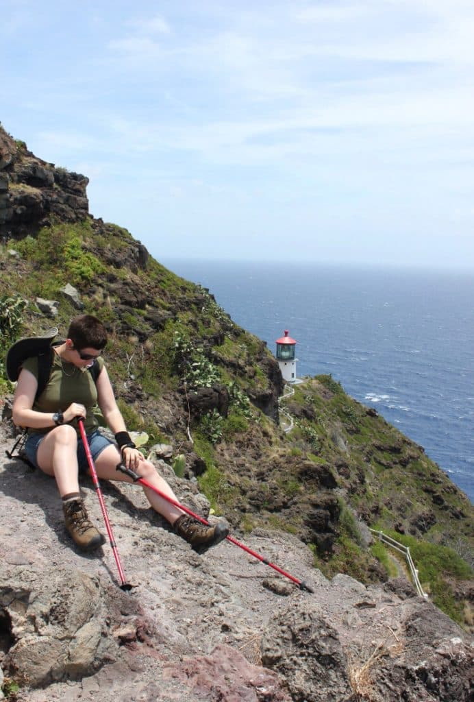 Hiker resting on a rock with Makapu'u Point lighthouse and the ocean in the background