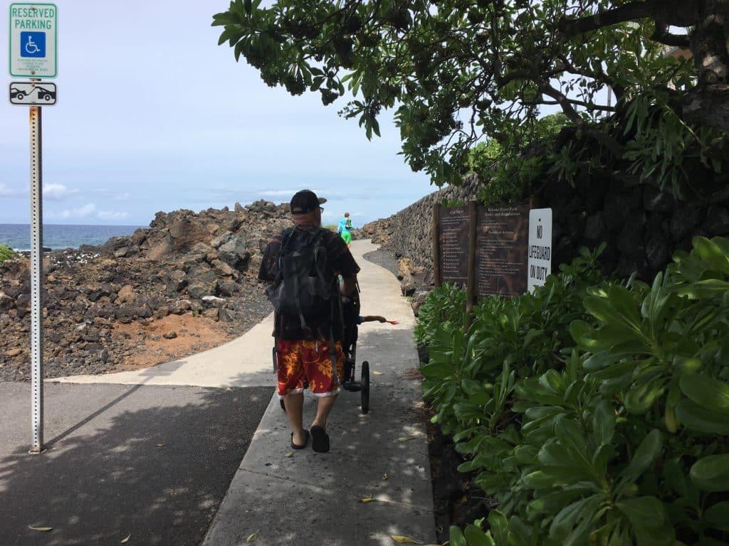 man pushing stroller on path to kukio beach